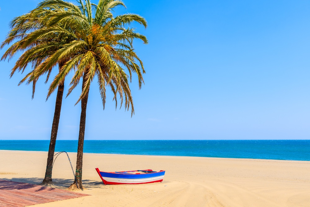 Vissersboot en palmbomen op zandstrand in de stad Estepona, Spanje.