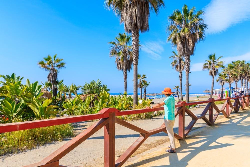 Jonge vrouw die zich op kustpromenade bevindt en mooi strand met palmbomen bekijkt bij Marbella, Andalusië, Spanje.
