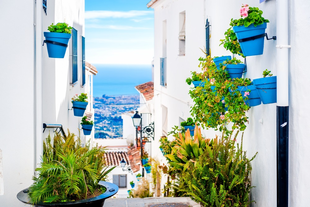 Pittoreske straat van Mijas Andalusië, met bloempotten in gevels. Andalusisch wit dorp. Costa de Sol. Zuid-Spanje