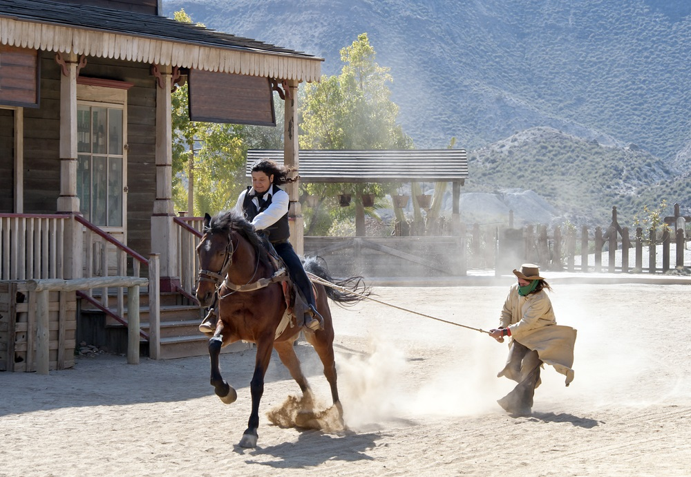 Cowboy sheriff slepen een bandiet door touw op Mini Hollywood, Tabernas, Provincie Almeria, Andalusië, Spanje.