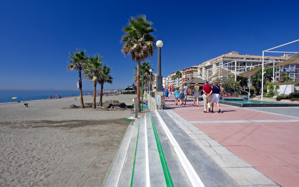 Zonnig zandstrand en boulevard bij Estepona in Zuid-Spanje aan de Costa del Sol. Estepona, Andalusië.
