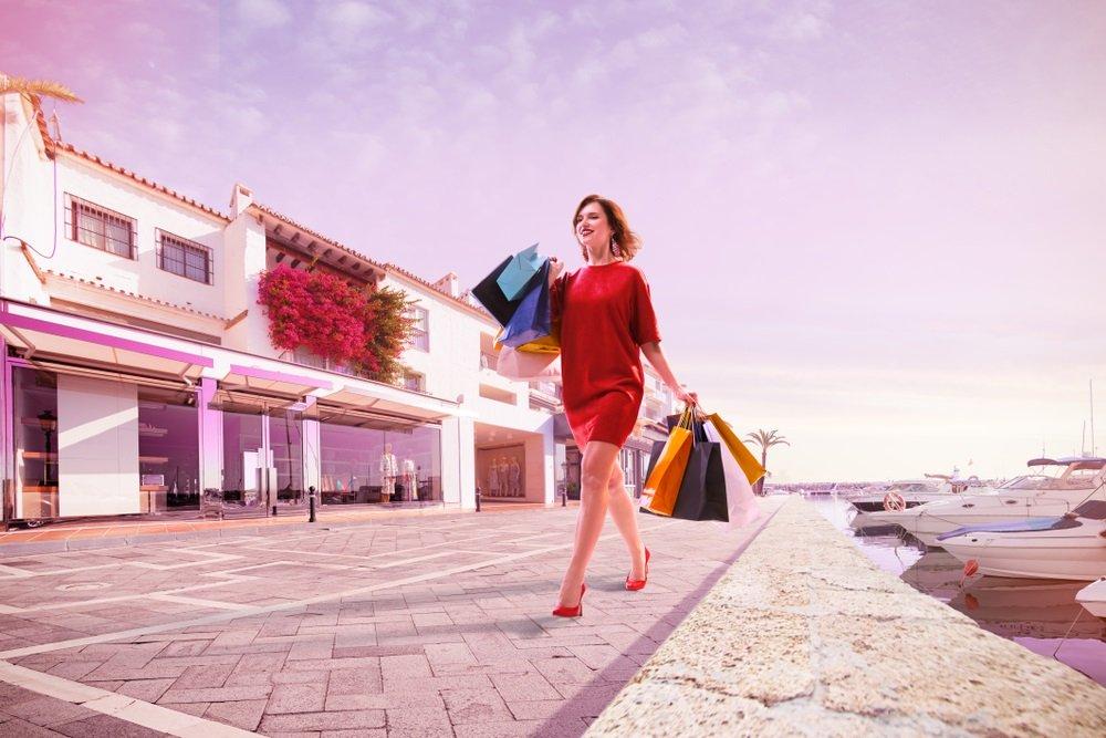 Mooie jongedame wandelt na succesvol winkelen in Puerto Banus, Spanje.