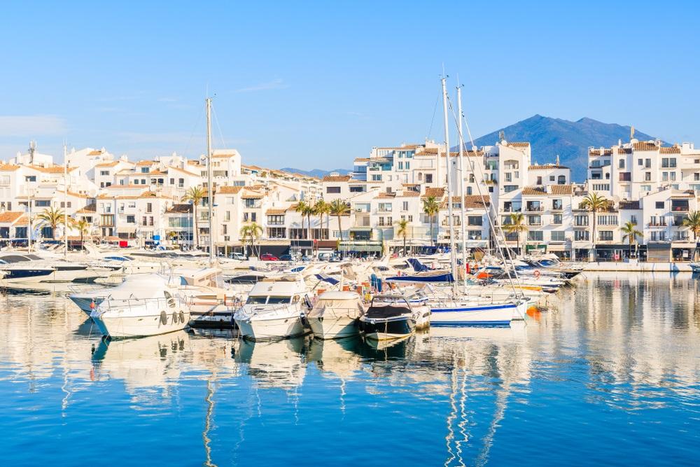 Uitzicht op de jachthaven van Puerto Banus met boten en witte huizen in de stad Marbella, Spanje bij zonsopgang, Andalusië.