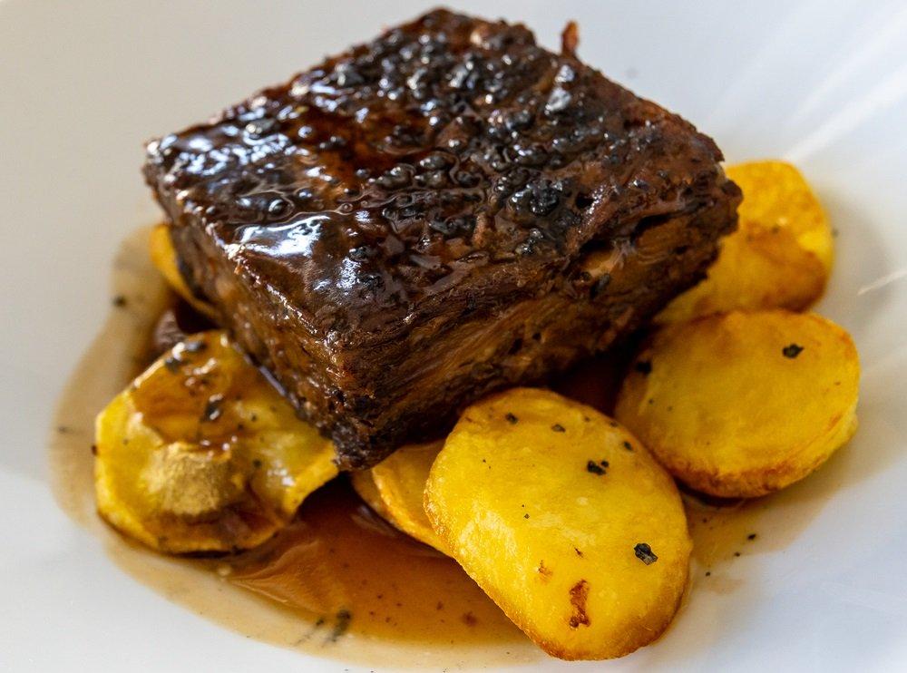 """traditionele Spaanse gerechten, gestoofde ossenstaart met aardappelen op een wit bord, plaatselijk bekend als """"rabo de toro"""", gerecht gevonden en gegeten in een restaurant in Ronda."""