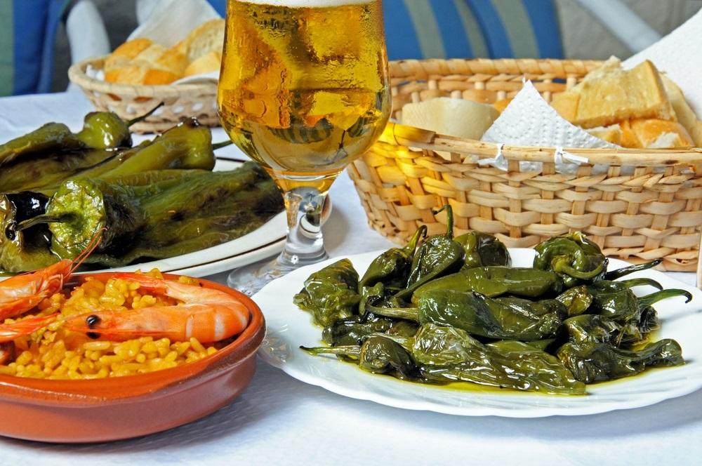 Padron-paprika's, gefrituurde puntpaprika's, paella met zeevruchten en varkensvlees, Costa del Sol, provincie Malaga, Andalusië, Spanje.