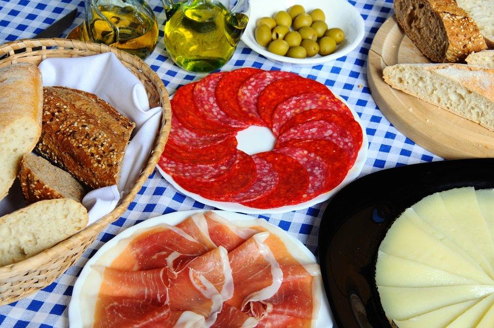 Selectie van tapas waaronder rustiek brood, Manchegokaas, Jamon Serrano (gezouten vlees), Salami en groene olijven, Costa del Sol, Andalusië, Spanje, West-Europa.
