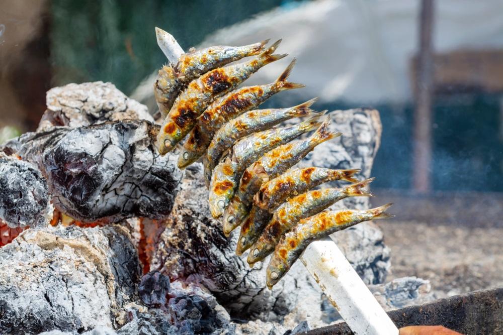 Sardines espeto, Malaga-stijl vis op stok barbecue, bereid op olijfboombrandhout op het strand. Malaga, Andalusië.