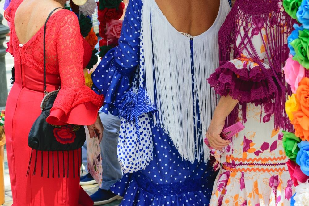 Malaga, Andalusië Drie blanke vrouwen die kleurrijke flamenco-jurken dragen in de straten van de stad op een zonnige zomerdag.