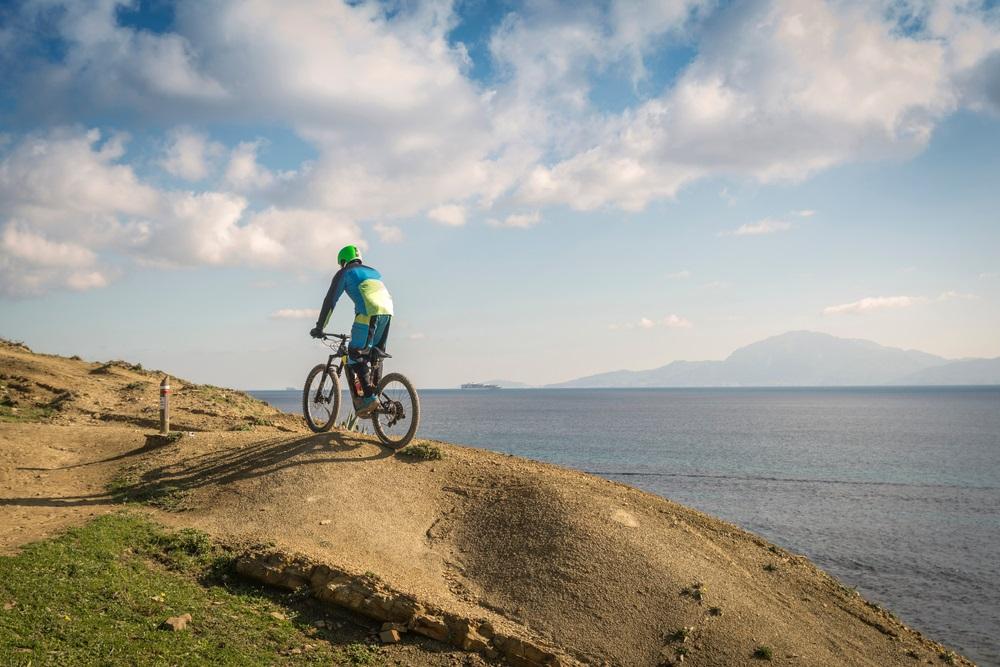 Jonge man beoefenen van extreme mountainbiken in het natuurpark Strait, Tarifa, provincie Cadiz, Andalusië, Spanje.