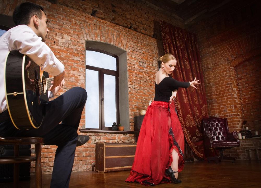 Jonge vrouw dansen flamenco in traditionele flamenco jurk en een man spelen de gitaar. Granada, Andalusië, Spanje.