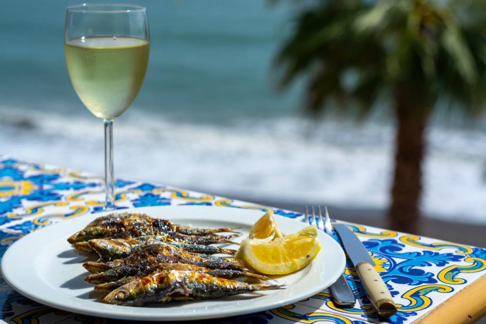 Sardines espeto, vis in Malaga-stijl op barbecue, bereid op brandhout van olijfbomen op het strand, geserveerd met witte wijn. Benalmadena, Spanje.