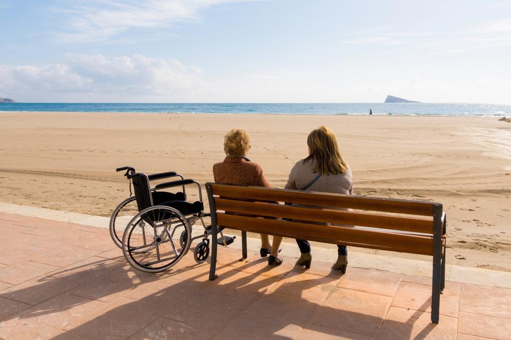 Oude vrouw zit met haar begeleidster aan de Costa del Sol. Zorgvakantie in Andalusië, Spanje.