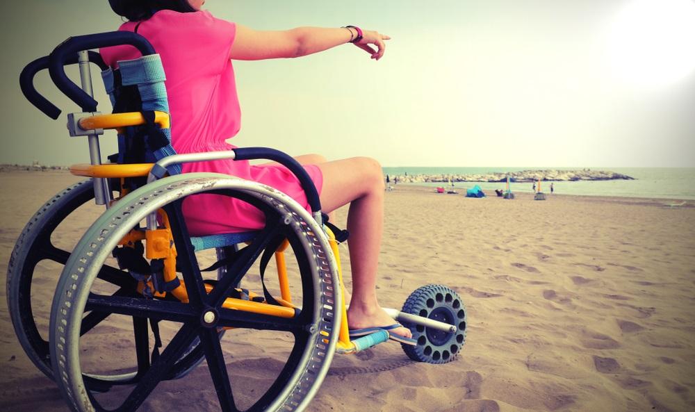 Meisje op de speciale rolstoel met grote wielen aan het zandstrand in de zomer met oud vintage tooneffect. Andalusië, Spanje.