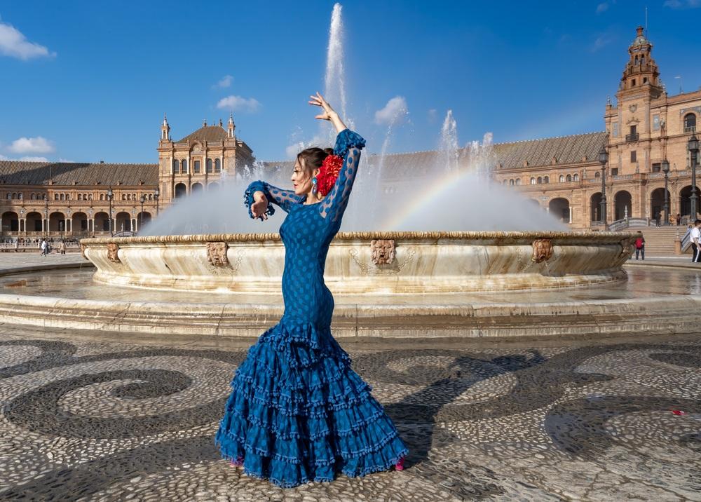 Typische en traditionele Andalusische en Spaanse vrouw flamenco dansen in Sevilla op een zonnige dag met blauwe lucht.