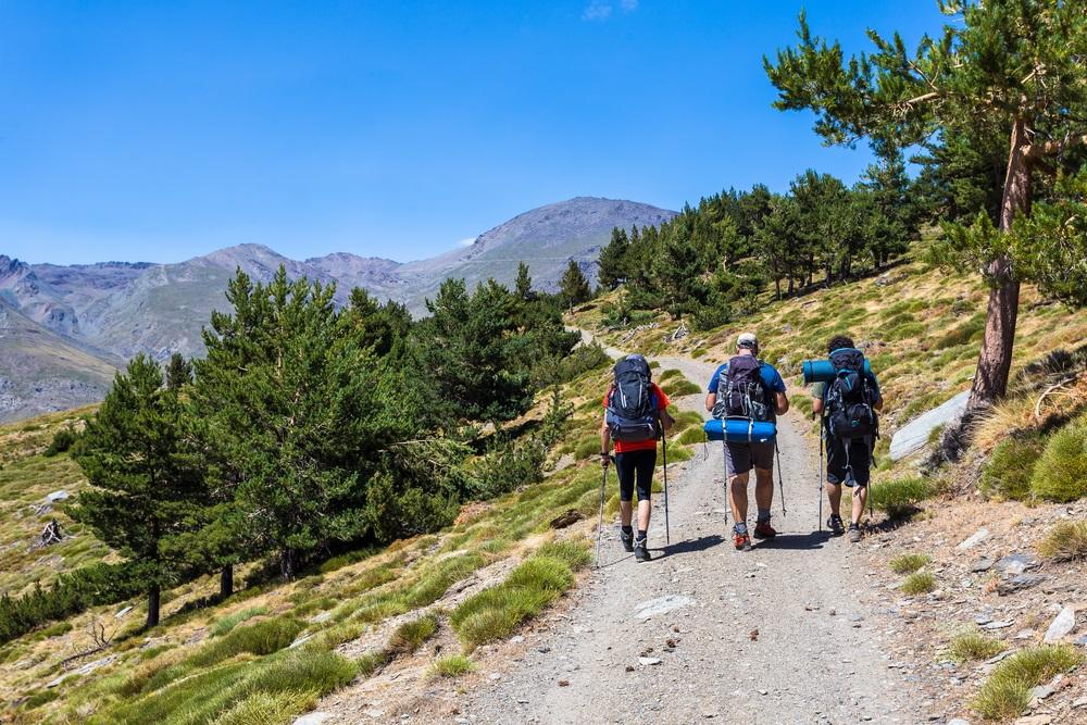 Drie wandelaars lopen 's ochtends over het pad dat naar Mulhacen leidt . Sierra Nevada, Spanje, Andalusië.