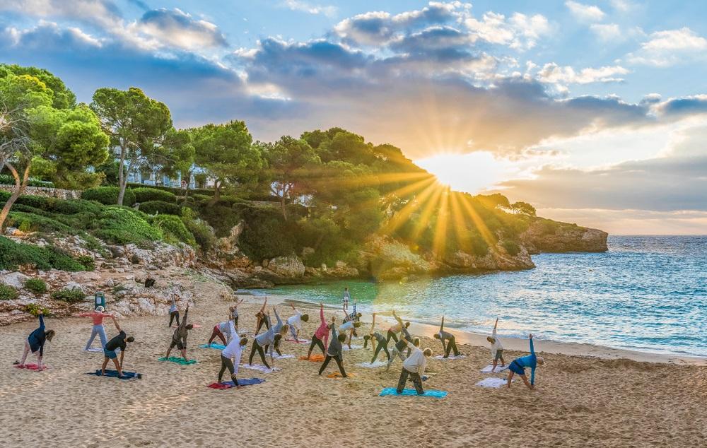 Mensen beoefenen van yoga bij zonsondergang aan het strand. Spirituele vakantie Andalusië.