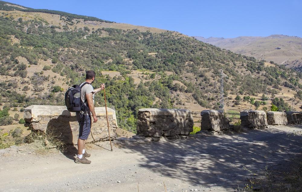 Trekker loopt langs de Poqueira-kloof vanuit Capilera, La Cebadilla genaamd. Regio Las Alpujarras, Granada, Spanje.
