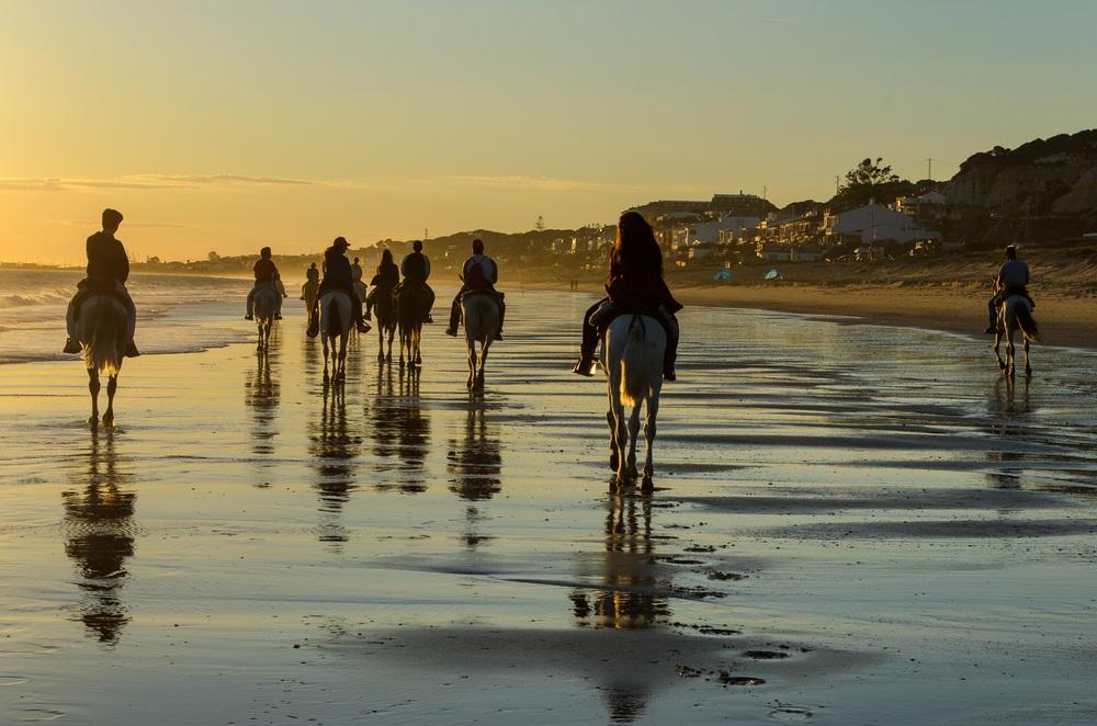 Paardrijden op het Mazagon-strand bij zonsondergang, Huelva, Spanje.
