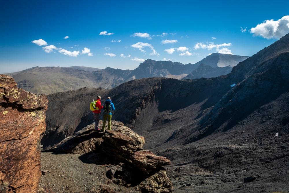 Achter mening van twee mannelijke reizigers die zich op rots bevinden en prachtige bergen bekijken op mooie zonnige dag in Sierra Nevada, Granada, Spanje.