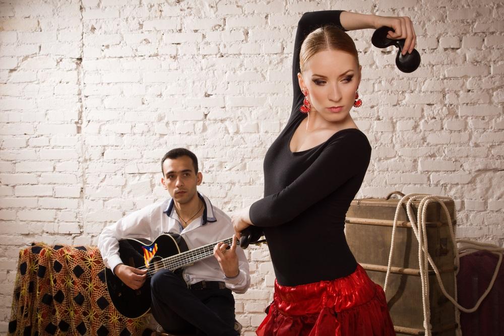 Jonge vrouw dansen flamenco in traditionele flamenco jurk en een man spelen de gitaar. Andalusië, Spanje.