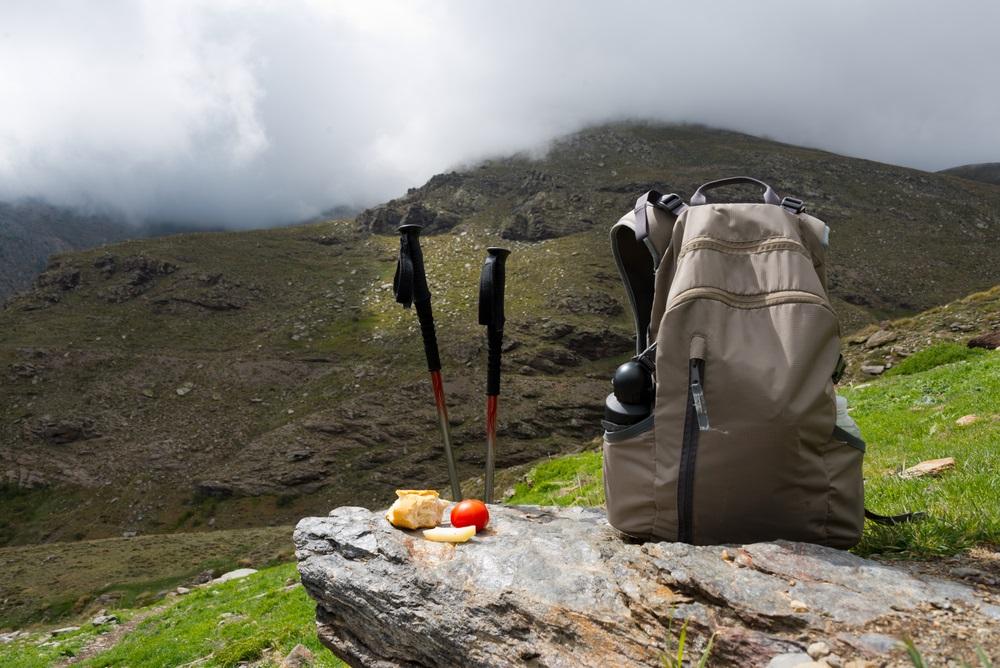Wandelstokken met lunch en rugzak bij bergketen in Sierra Nevada, Spanje, Andalusië.