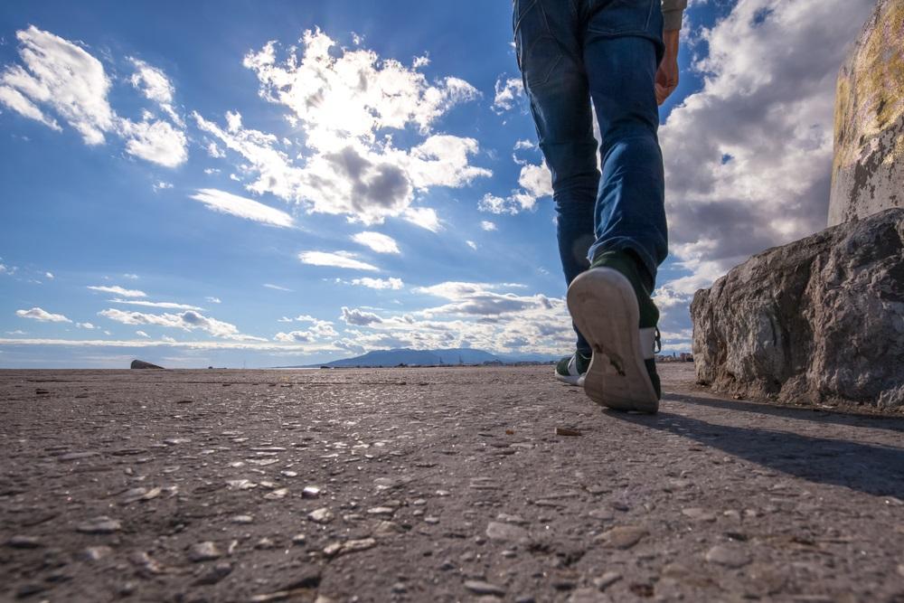 Man loopt langs de kust tijdens een zonnige dag. Benen en bezinksel lopen op een stenen pad met op de achtergrond een blauwe lucht met wolken.