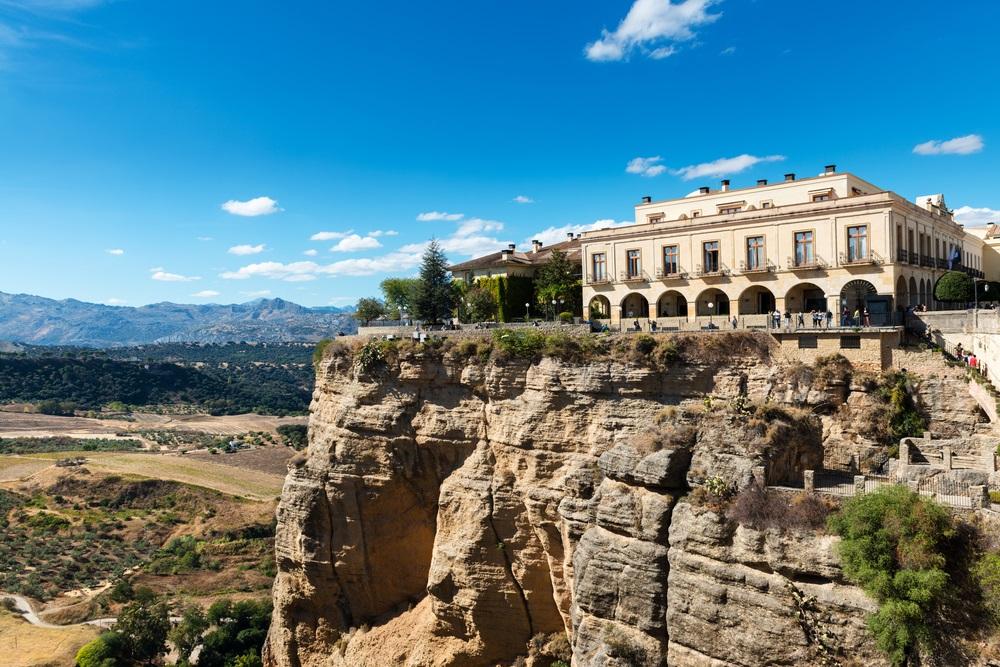Zijaanzicht van de beroemde Parador, gebouwd over de klif van de rivier de Guadalevin in het Andalusische dorp Ronda, Spanje, gezien vanaf de Puente Nuevo-brug. Paradores hotels.