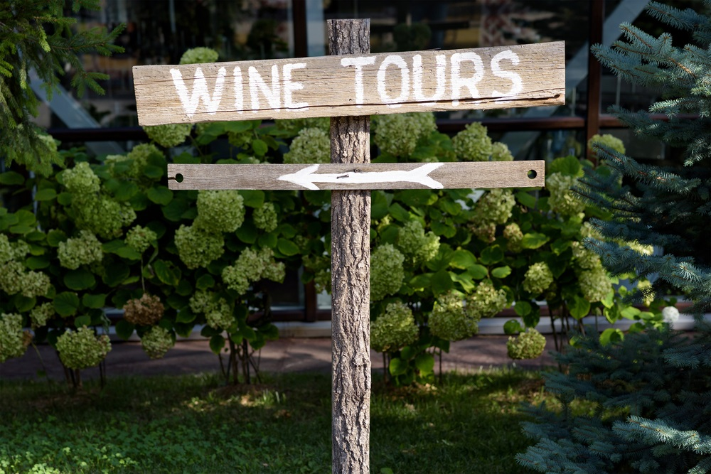 Houten wijntour bord met pijl met groene struiken op achtergrond.