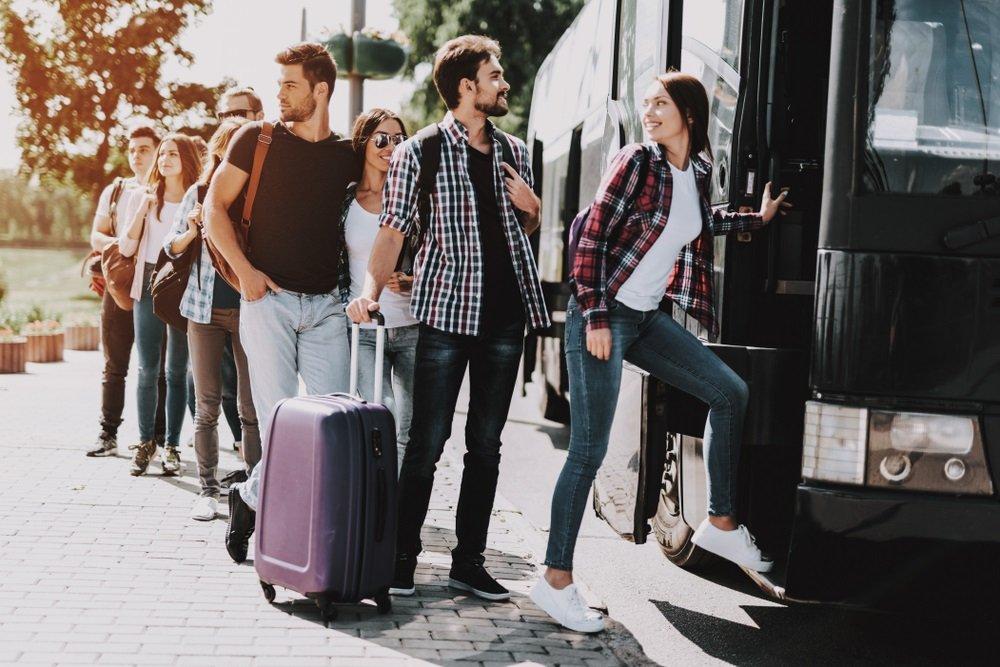 Een groepsrondreis door Andalusië; jonge mensen stappen in de bus.