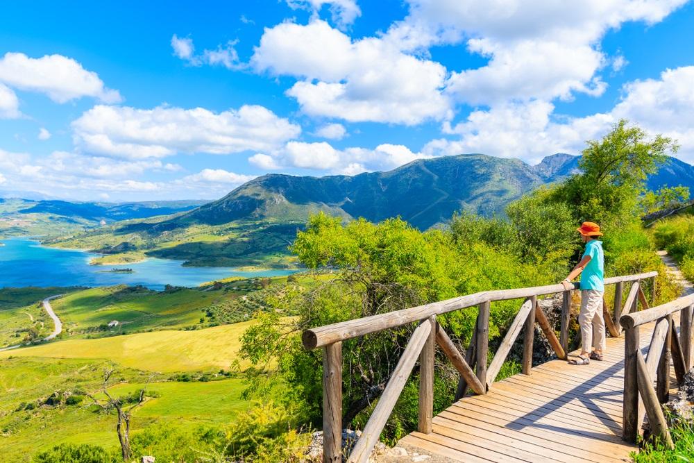 Jonge vrouwentoerist die zich op brug dichtbij kasteeltoren bevinden op wandelpad in het dorp Zahara de la Sierra, Andalusië, Spanje.